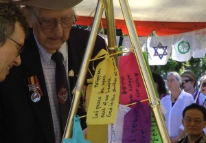 Members of the community attaching their wish for peace to Peace Sculpture. Anzac Day 2013